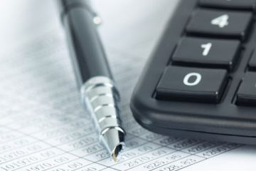 calculator and pen with financial documents